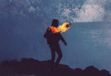 silhouette of man holding fire torch